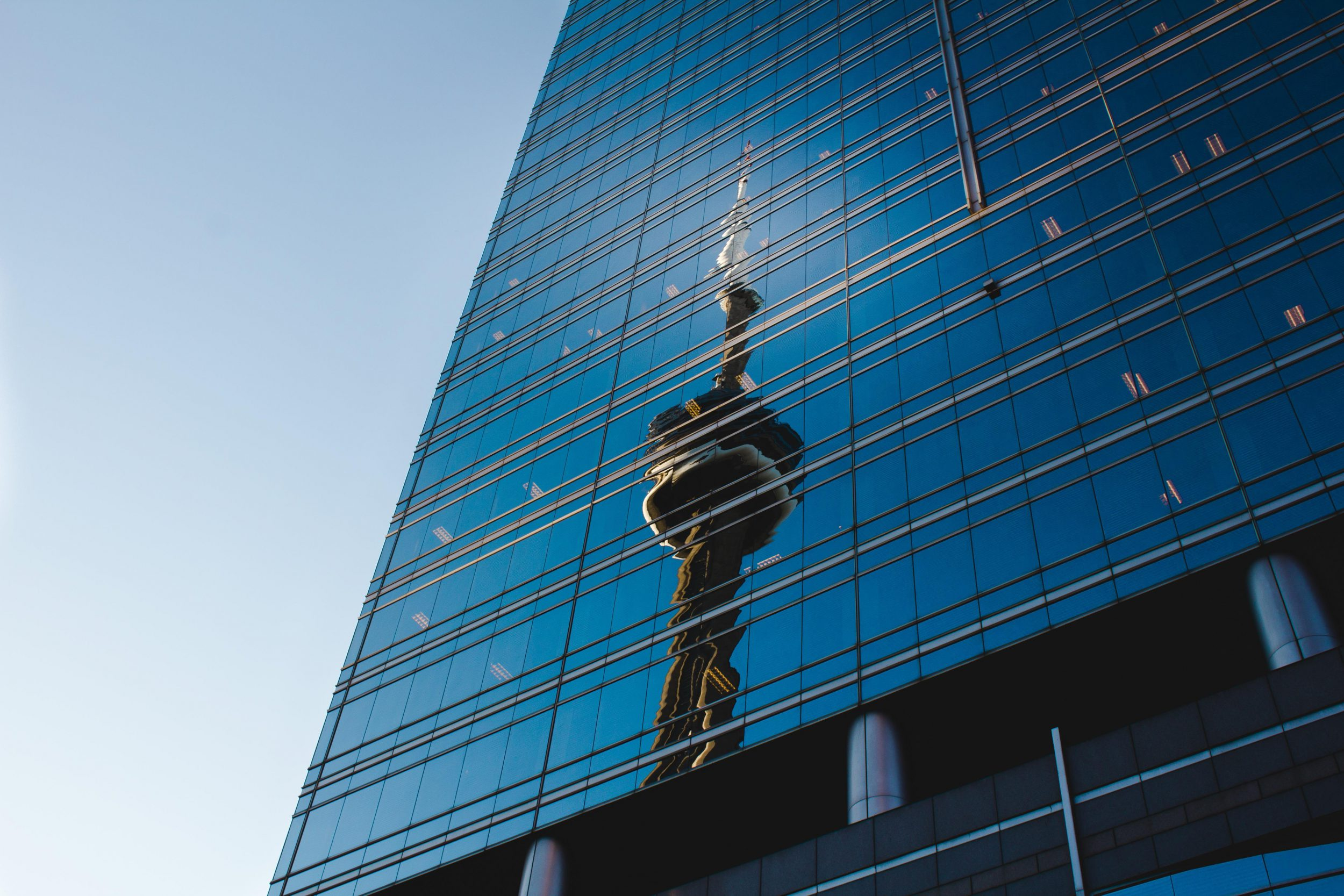 CN tower reflected on a glass building